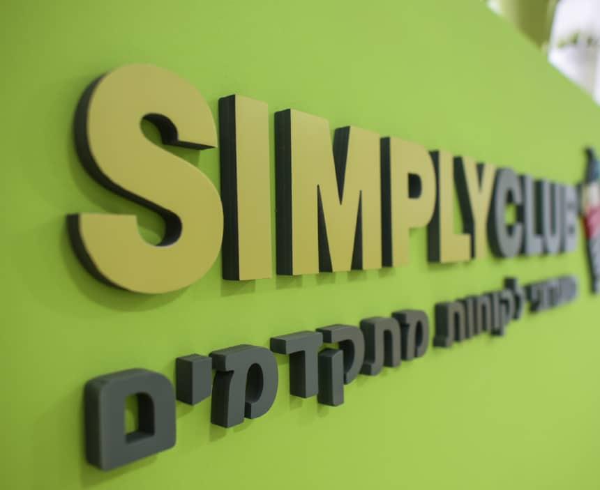 לוגו של סימפלי קלאב על קיר בצבע ירוק
